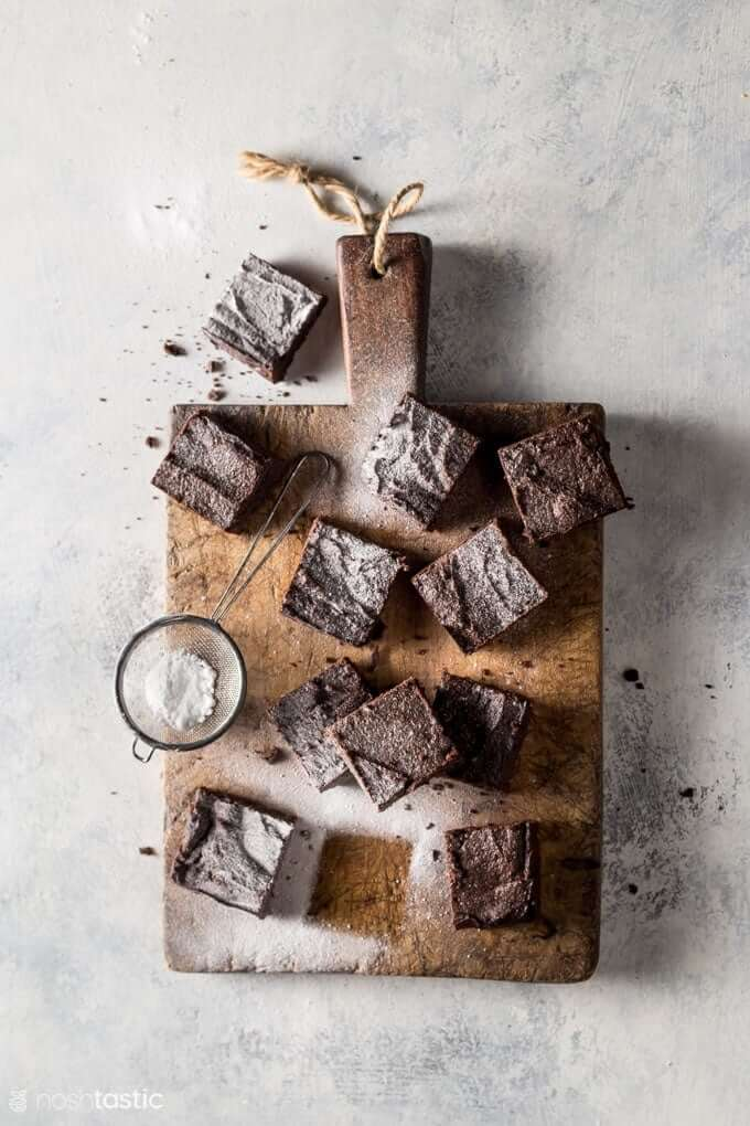 brownies on cutting board with powdered sugar dusting