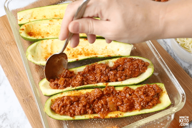 scooping meat sauce into zucchini boats
