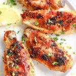 crispy lemon pepper chicken wings on white plate with lemon wedge