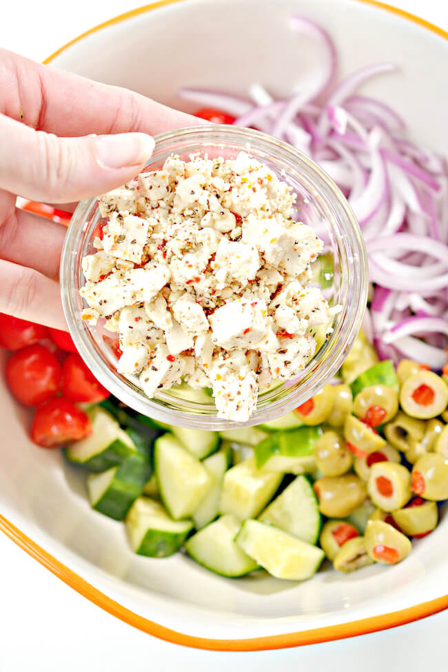 adding feta cheese to mixing bowl of Greek salad ingredients