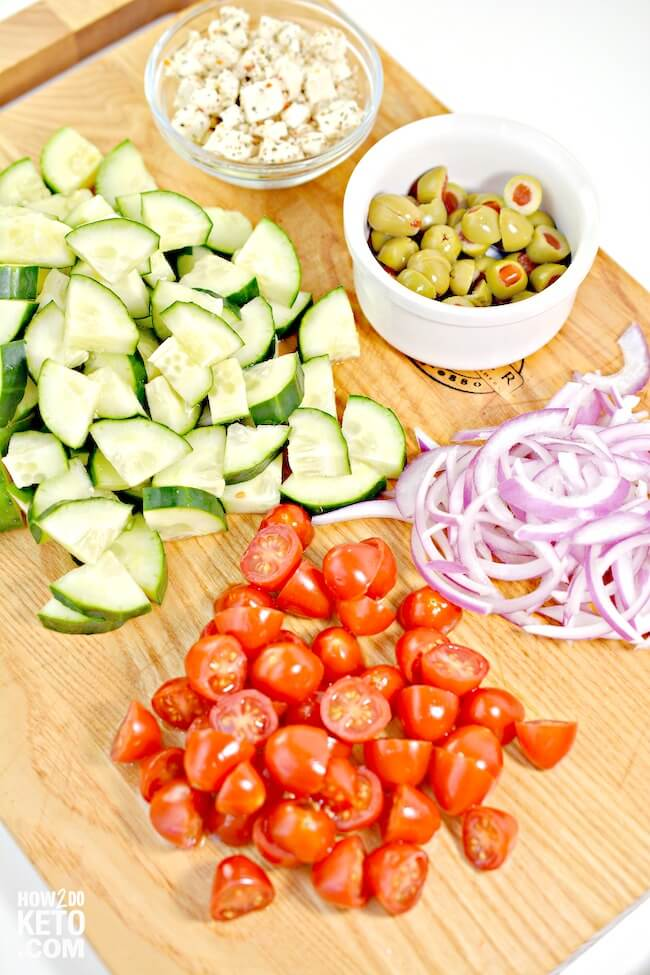 chopped Greek salad ingredients on cutting board