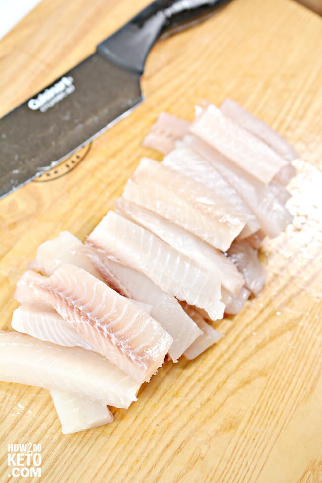 cutting tilapia into strips for frying