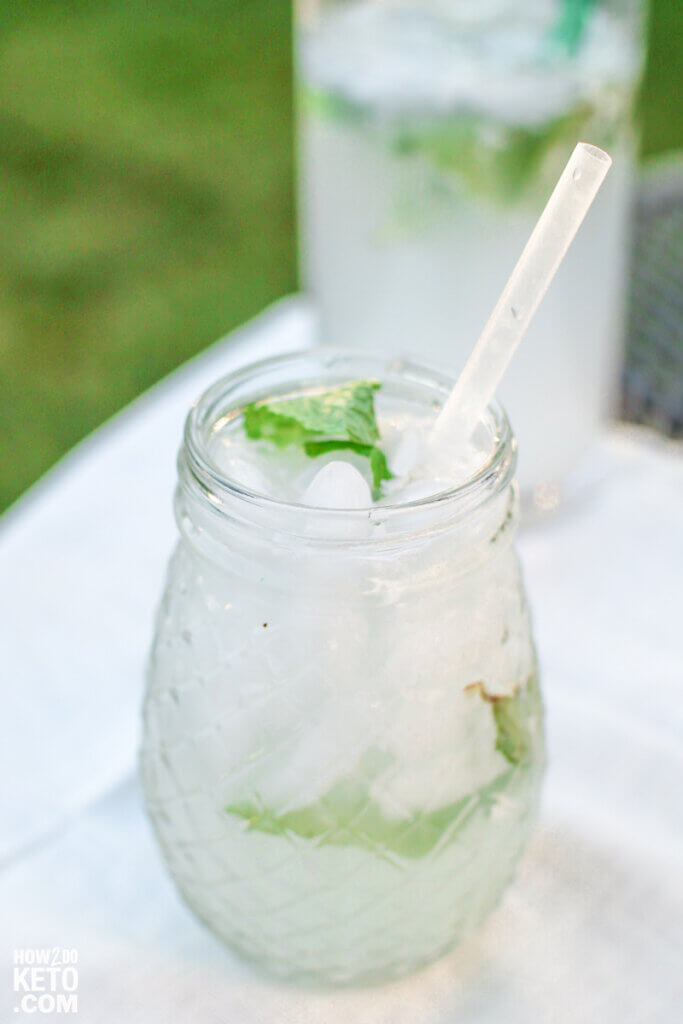mojito glass on table with a pitcher inn background