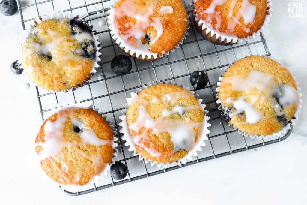 keto lemon blueberry muffins surrounded by blueberries