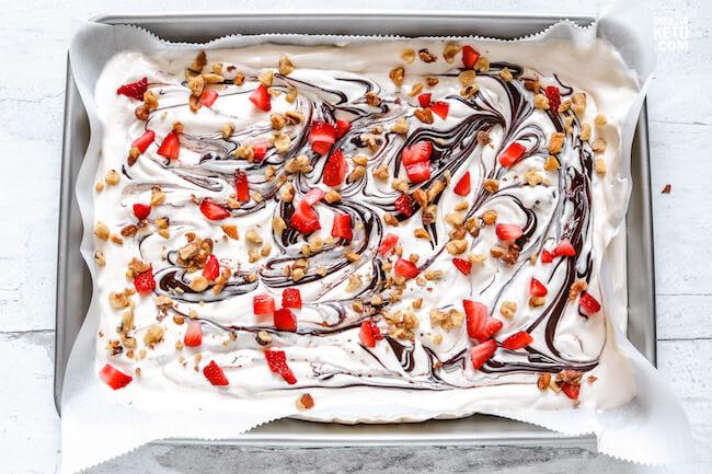 sprinkling strawberries & walnuts on top of cheesecake bark