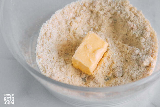 almond flour in mixing bowl with stick of butter