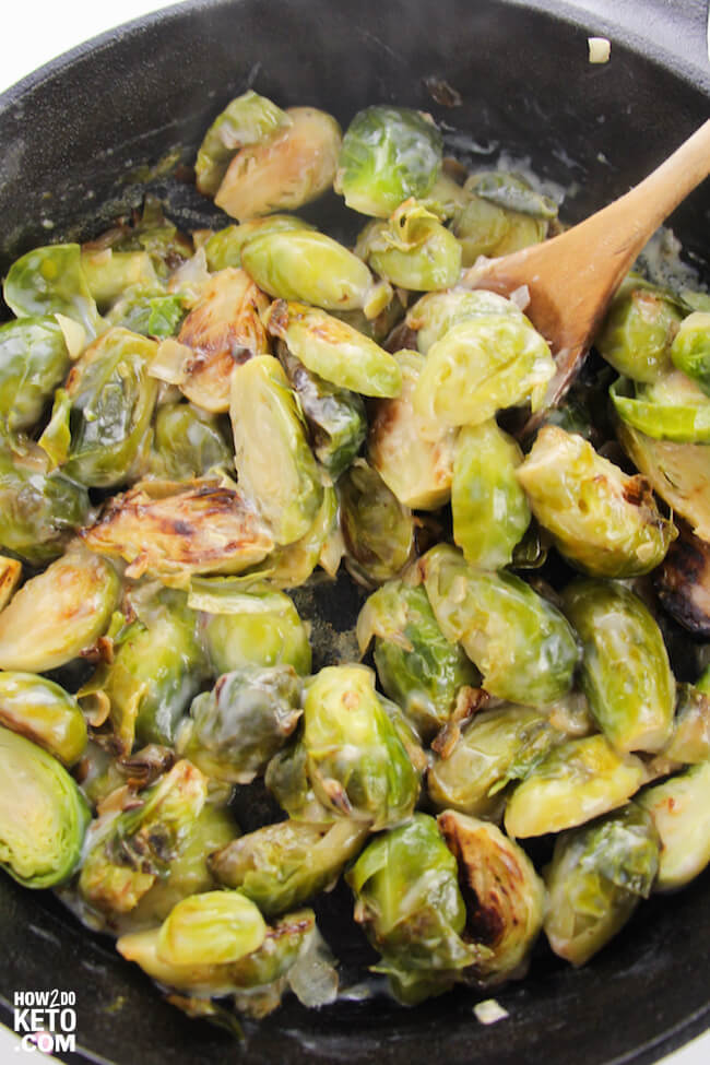 stirring creamy brussel sprouts in iron skillet
