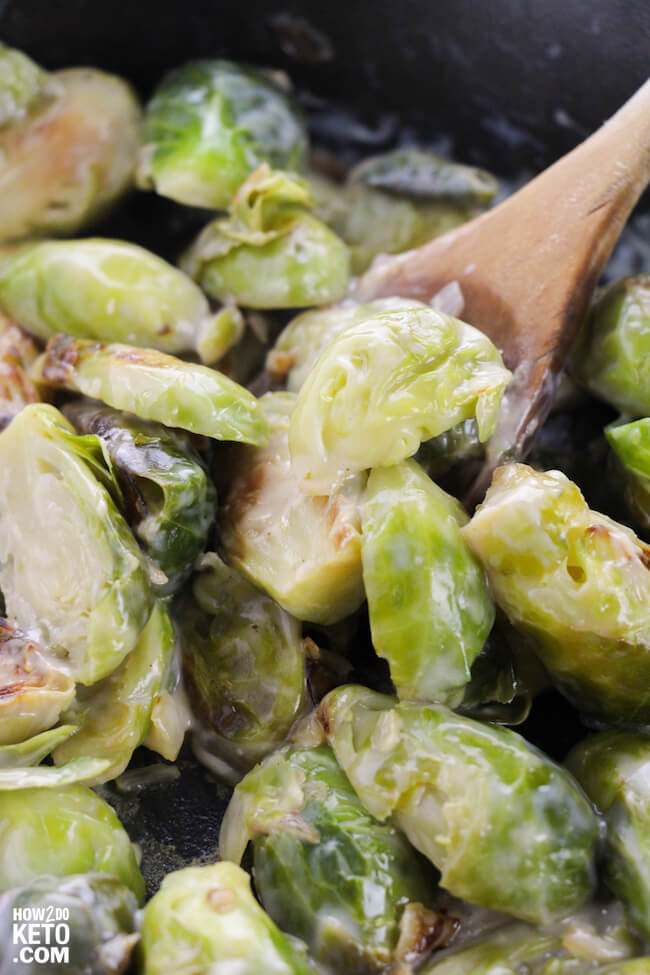 close up of creamy brussel sprouts on wooden spoon in skillet