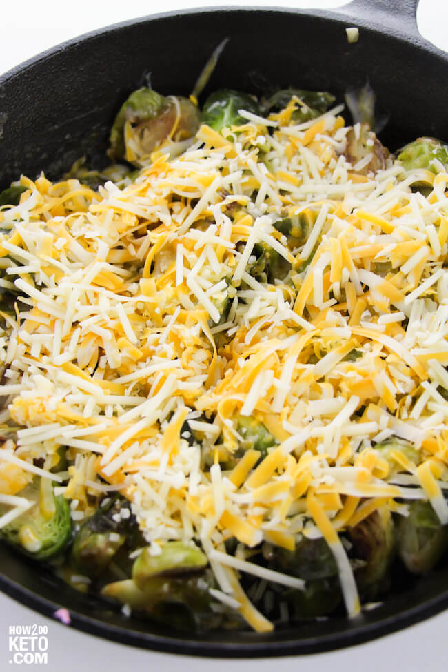 iron skillet with brussel sprouts covered in shredded cheese