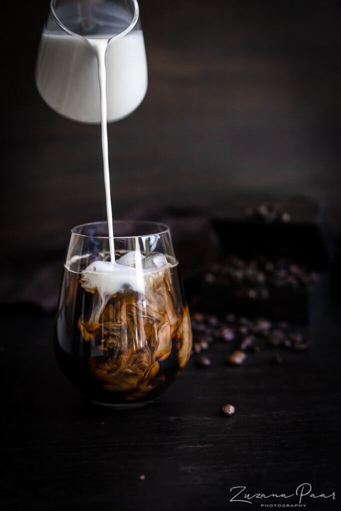 pouring milking into glass of coffee