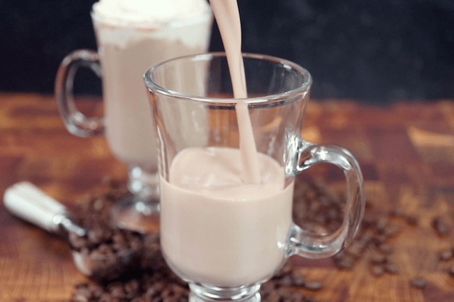 pouring chocolate almond milk into glass mug