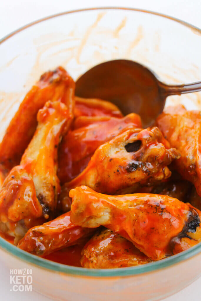 stirring chicken wings in buffalo sauce