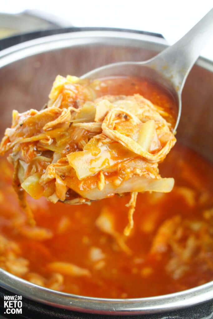 scooping cooked enchilalada chicken from Instant Pot