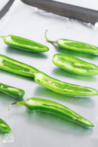 halved jalapeño peppers on baking sheet
