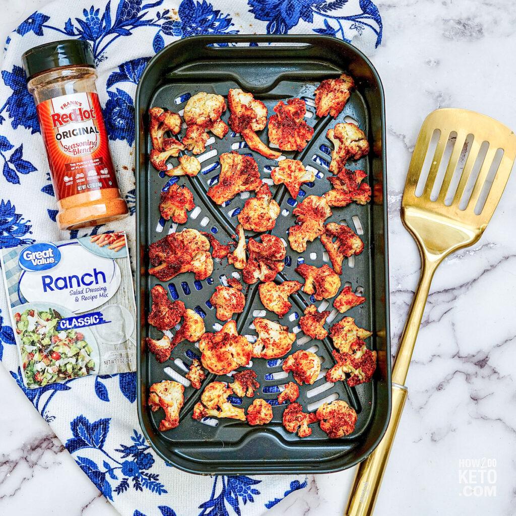 Buffalo seasoned Cauliflower florets on air fryer pan
